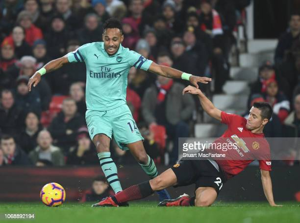 PierreEmerick Aubameyang of Arsenal is challenged by Ander Herrera of Manchester United during the Premier League match between Manchester United and...