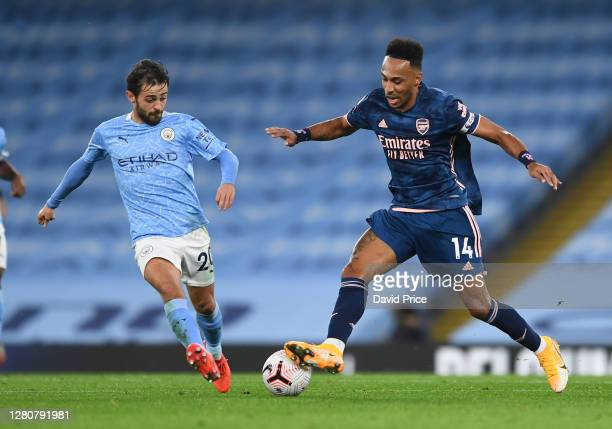 PierreEmerick Aubameyang of Arsenal is challenged by Bernardo Silva of Man City during the Premier League match between Manchester City and Arsenal...
