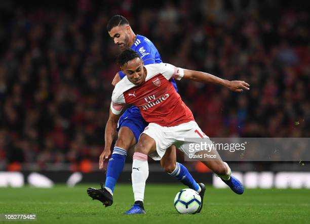 PierreEmerick Aubameyang of Arsenal is challenged by Rachid Ghezzal of Leicester during the Premier League match between Arsenal FC and Leicester...