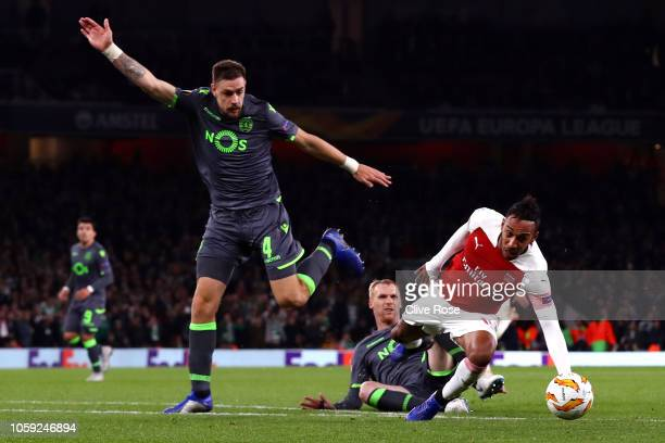 Pierre-Emerick Aubameyang of Arsenal is fouled by Jeremy Mathieu of Sporting CP who is sent off as Sebastian Coates of Sporting CP moves in during...