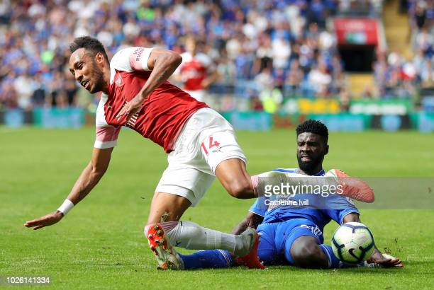 PierreEmerick Aubameyang of Arsenal is tackled by Bruno Ecuele Manga of Cardiff City during the Premier League match between Cardiff City and Arsenal...