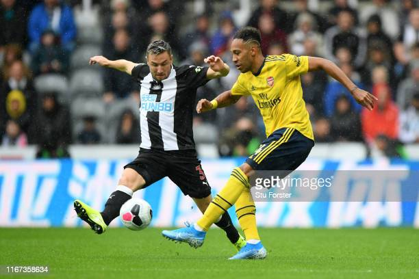 PierreEmerick Aubameyang of Arsenal passes he ball under pressure from Paul Dummett of Newcastle United during the Premier League match between...