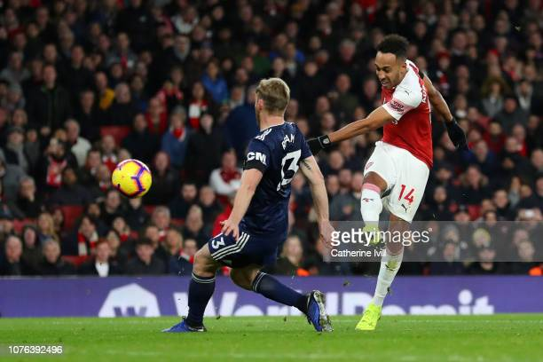PierreEmerick Aubameyang of Arsenal scores his team's fourth goal past Tim Ream of Fulham during the Premier League match between Arsenal FC and...