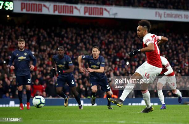 PierreEmerick Aubameyang of Arsenal scores his team's second goal from the penalty spot during the Premier League match between Arsenal FC and...