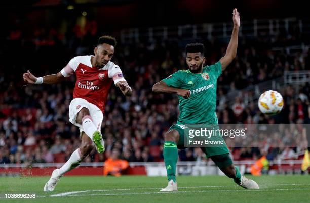 PierreEmerick Aubameyang of Arsenal scores his team's third goal as Artur Sergio Batista de Souza of Vorskla Poltava attempts to block during the...