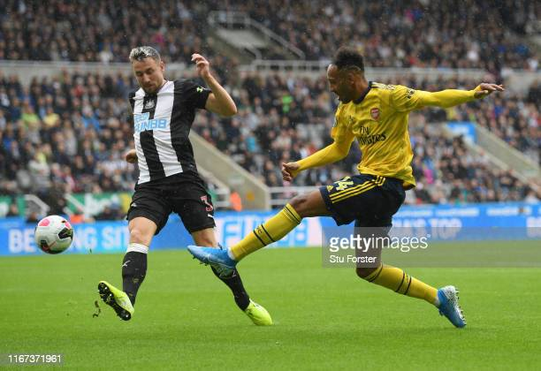 PierreEmerick Aubameyang of Arsenal shoots for goal under pressure from Paul Dummett of Newcastle United during the Premier League match between...