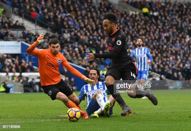 PierreEmerick Aubameyang of Arsenal skips past Matthew Ryan and Ezequiel Schelotto of Brighton during the Premier League match between Brighton and...