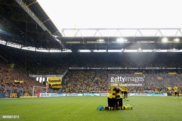 PierreEmerick Aubameyang of Borussia Dortmund celebrates scoring his teams forth and winning goal of the game with team mate Marco Reus during the...