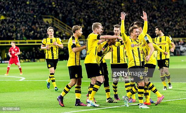 PierreEmerick Aubameyang of Borussia Dortmund celebrates with team mates after scoring his team's first goal during the Bundesliga match between...