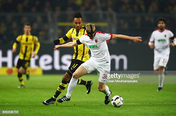 PierreEmerick Aubameyang of Borussia Dortmund challenges Martin Hinteregger of FC Augsburg during the Bundesliga match between Borussia Dortmund and...