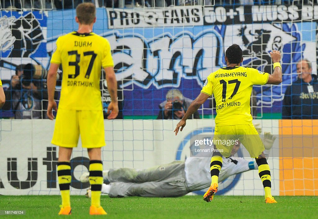 Pierre-Emerick Aubameyang (R) of Borussia Dortmund scores the opening goal past goal-keeper Garbor Kiraly (C) of 1860 Muenchen with a penalty-kick during the DFB Cup match between TSV 1860 Muenchen and Borussia Dortmund at Allianz Arena on September 24, 2013 in Munich, Germany.