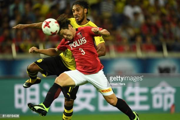 Pierre-Emerick Aubameyang of Burussia Dortmund and Tomoya Ugajin of Urawa Red Diamonds compete for the ball during the preseason friendly match...