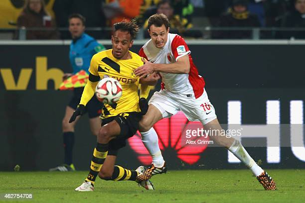 PierreEmerick Aubameyang of Dortmund battles for the ball with Christoph Janckern of Augsburg during the Bundesliga match between Borussia Dortmund...