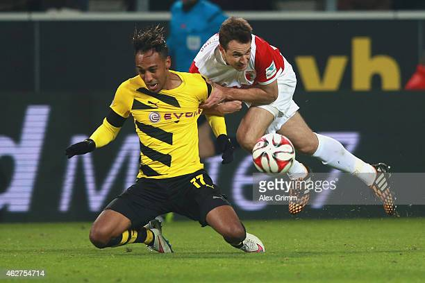 PierreEmerick Aubameyang of Dortmund battles for the ball with Christoph Janckern of Augsburg during the Bundesliga match between Borussia Dortmund...