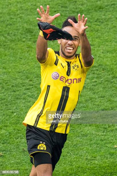 PierreEmerick Aubameyang of Dortmund catches his mask after scoring his teams first goal during the Bundesliga match between FC Schalke 04 and...