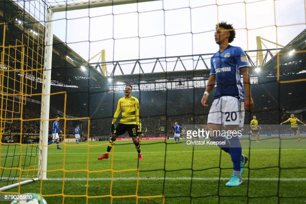 Pierre-Emerick Aubameyang of Dortmund celebrates after Mario Goetze of Dortmund scored a goal to make it 3:0, while Thilo Kehrer of Schalke looks on,...