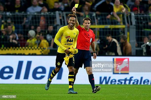 PierreEmerick Aubameyang of Dortmund celebrates the third goal with a batman shirt and referee Felix Brych shows him the yellow card during the...