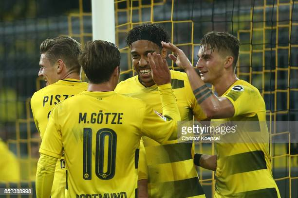 PierreEmerick Aubameyang of Dortmund celebrates with Maximilian Philipp of Dortmund and Mario Goetze of Dortmund after he scored his teams third goal...