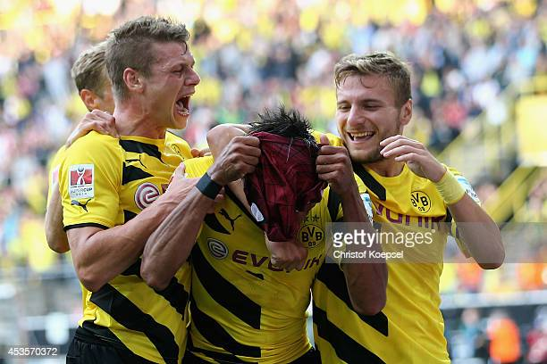 PierreEmerick Aubameyang of Dortmund puts on his spider mask to celebrate the second goal with Lukasz Piszczek and Ciro Immobile of Dortmund during...