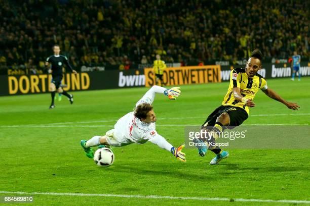 PierreEmerick Aubameyang of Dortmund scores the third goal against Rene Adler of Hamburg during the Bundesliga match between Borussia Dortmund and...