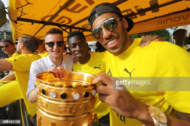 PierreEmerick Aubameyang Ousmane Dembele and Marco Reus of Borussia Dortmund lift the DFB Cup trophy as the team celebrates during a winner's parade...