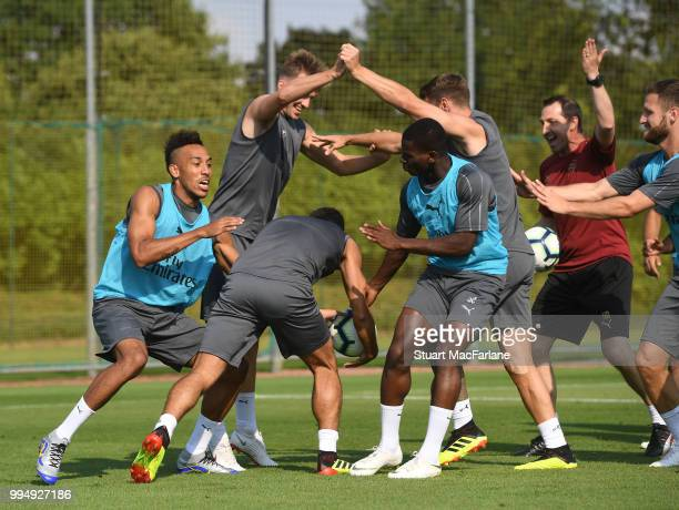 PierreEmerick Aubameyang Rob Holding Henrikh Mkhitaryan Jordi OseiTutu and Aaron Ramsey of Arsenal share a joke during a training session at London...