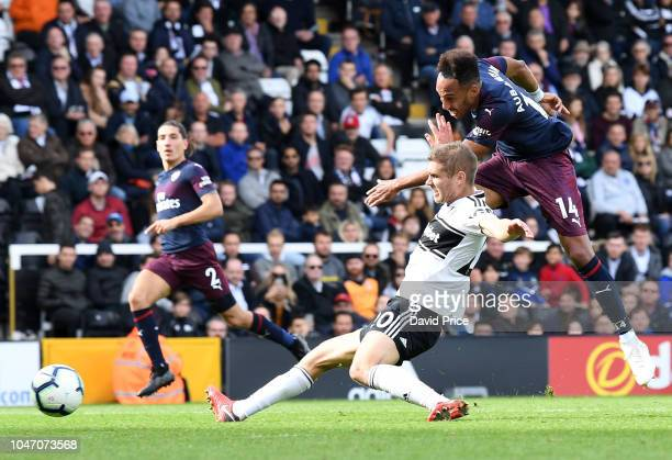 PierreEmerick Aubameyang scores Arsenal's 5th goal under pressure from Maxime Le Marchard of Fulham during the Premier League match between Fulham FC...