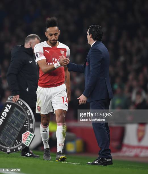 PierreEmerick Aubameyang shakes hands with Arsenal Head Coach Unai Emery after his substitution during the Premier League match between Arsenal FC...