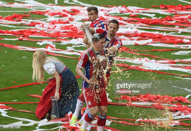 PierreEmile Hojbjerg of Bayern Muenchen is showered with beer by Daniel van Buyten to celebrate winning the German Bundesliga Championship after the...