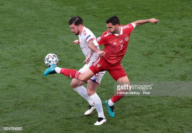 Pierre-Emile Hojbjerg of Denmark and Magomed Ozdoev of Russia battle for possession during the UEFA Euro 2020 Championship Group B match between...