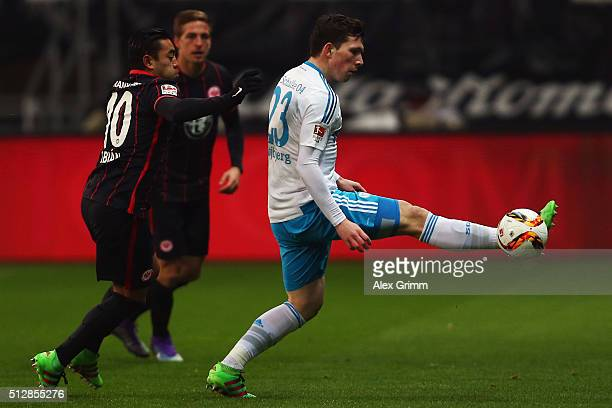 PierreEmile Hojbjerg of Schalke is challenged by Marco Fabian of Frankfurt during the Bundesliga match between Eintracht Frankfurt and FC Schalke 04...