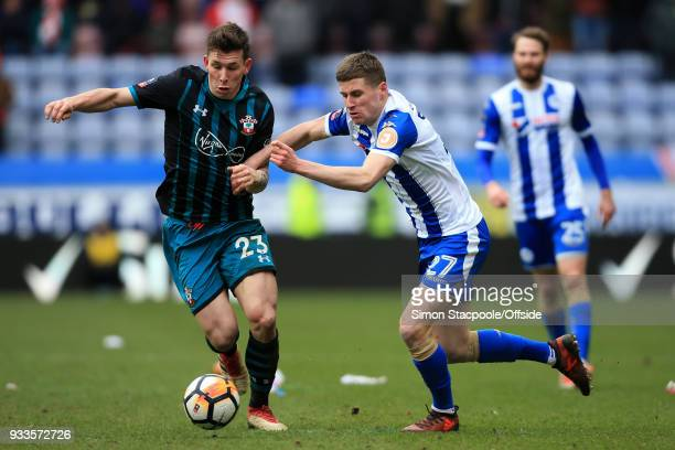 PierreEmile Hojbjerg of Southampton battles with Ryan Colclough of Wigan during The Emirates FA Cup Quarter Final match between Wigan Athletic and...