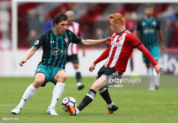 PierreEmile Hojbjerg of Southampton is tackled by Ryan Woods of Brentford during the Pre Season Friendly match between Brentford and Southampton at...