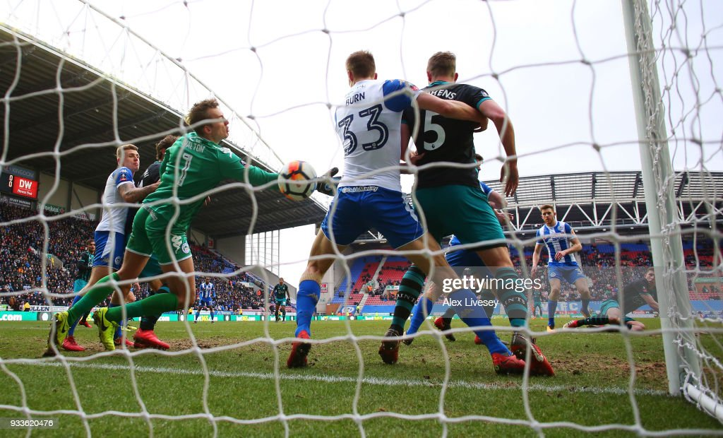 Pierre-Emile Hojbjerg of Southampton (R) scores their first goal past goalkeeper Christian Walton of Wigan Athletic during The Emirates FA Cup Quarter Final match between Wigan Athletic and Southampton at DW Stadium on March 18, 2018 in Wigan, England.