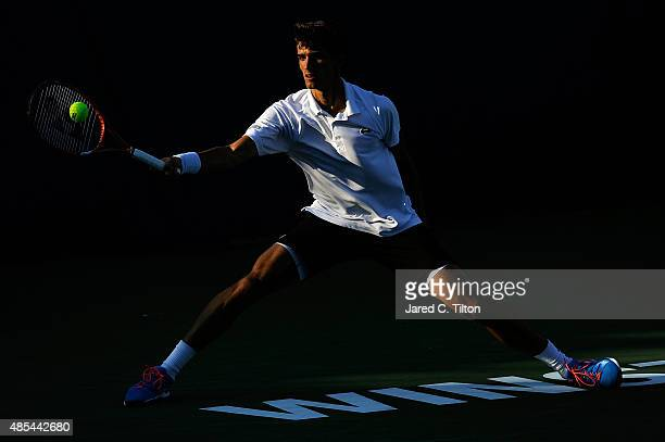 Pierre-Hugues Herbert of France returns a shot from Pablo Carreno Busta of Spain during the fourth day of the Winston-Salem Open at Wake Forest...