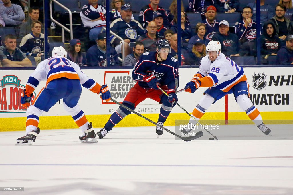 Pierre-Luc Dubois #18 of the Columbus Blue Jackets attempts to skate the puck past Jason Chimera #25 of the New York Islanders and Brock Nelson #29 of the New York Islanders during the third period on October 6, 2017 at Nationwide Arena in Columbus, Ohio. Columbus defeated New York 5-0.