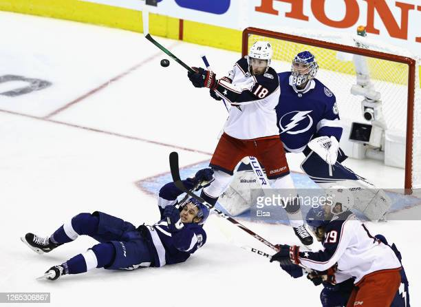 Pierre-Luc Dubois of the Columbus Blue Jackets bats the puck as Mitchell Stephens and Andrei Vasilevskiy of the Tampa Bay Lightning defend the net...