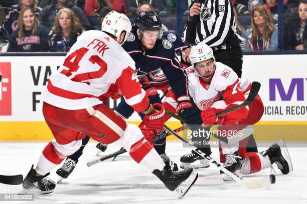 PierreLuc Dubois of the Columbus Blue Jackets battles to skate the puck between Martin Frk and Dylan Larkin of the Detroit Red Wings during the third...