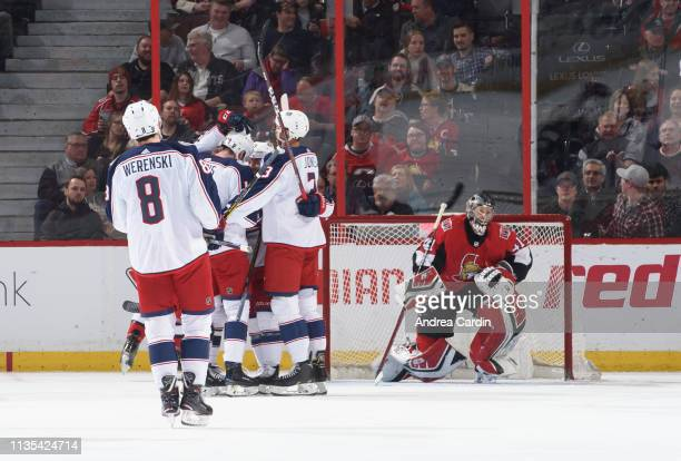 Pierre-Luc Dubois of the Columbus Blue Jackets celebrates with teammates Zach Werenski and Seth Jones after scoring his second goal of the period...