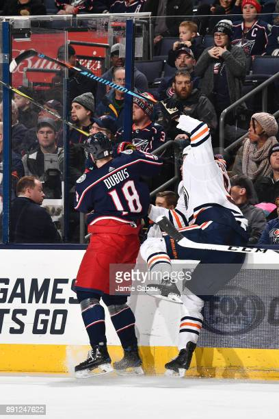 PierreLuc Dubois of the Columbus Blue Jackets checks Jesse Puljujarvi of the Edmonton Oilers into the boards during the third period of a game on...