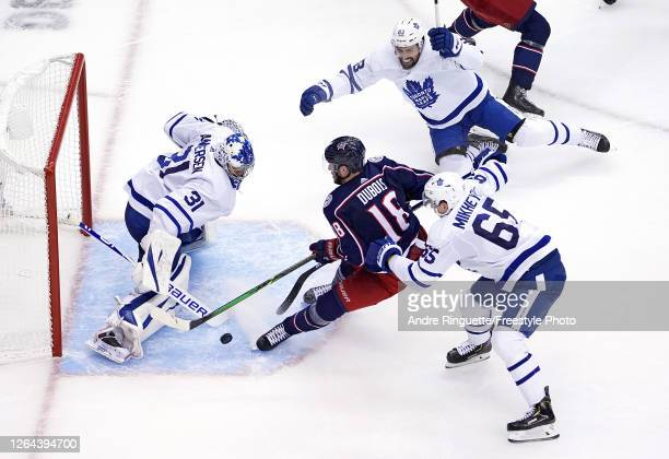 Pierre-Luc Dubois of the Columbus Blue Jackets gets hit by Ilya Mikheyev of the Toronto Maple Leafs as he attempts a shot on Frederik Andersen during...
