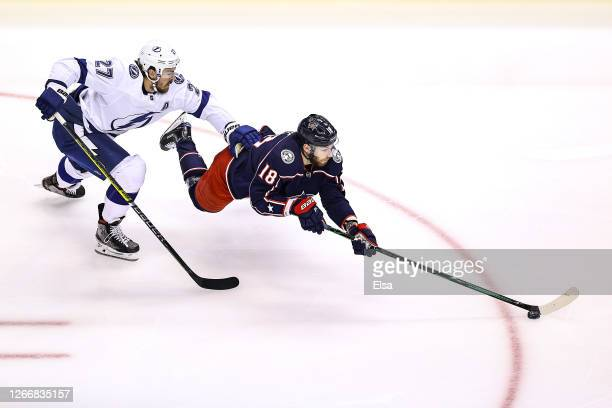 Pierre-Luc Dubois of the Columbus Blue Jackets gets tripped up against Ryan McDonagh of the Tampa Bay Lightning during the first period in Game Four...