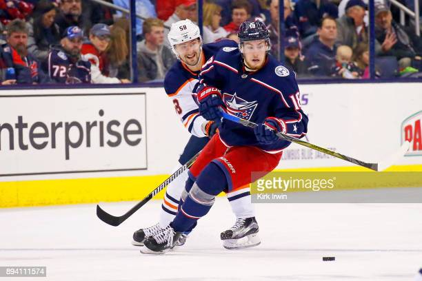 PierreLuc Dubois of the Columbus Blue Jackets skates the puck away from Anton Slepyshev of the Edmonton Oilers during the game on December 12 2017 at...