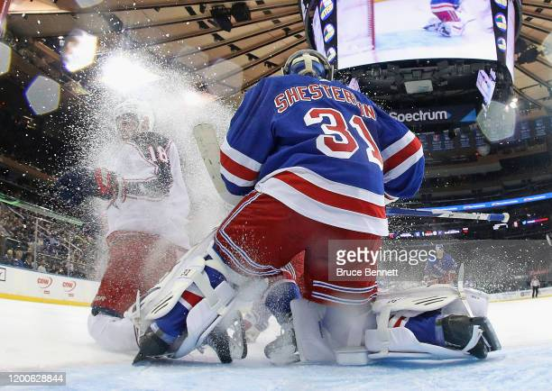 Pierre-Luc Dubois of the Columbus Blue Jackets slides into Igor Shesterkin of the New York Rangers during the second period at Madison Square Garden...