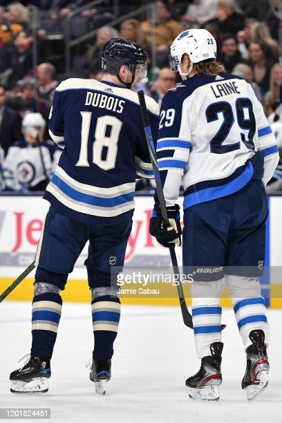 Pierre-Luc Dubois of the Columbus Blue Jackets talks with Patrik Laine of the Winnipeg Jets during a break in action on January 22, 2020 at...