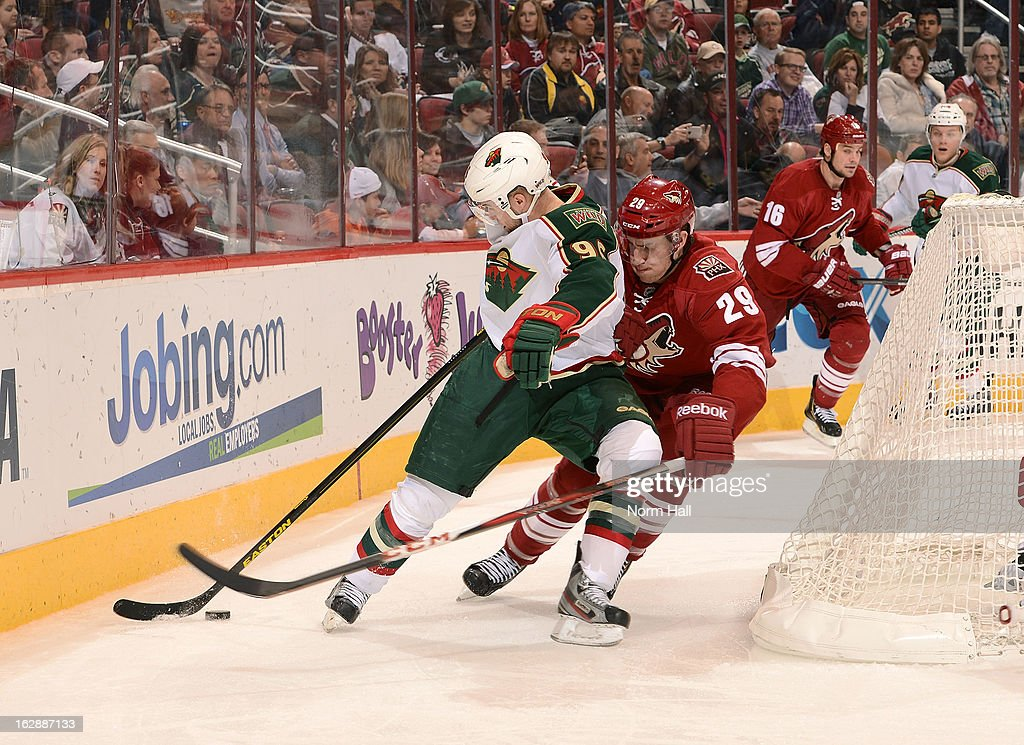 Pierre-Marc Bouchard #96 of the Minnesota Wild tries to work the puck behind the net around Michael Stone #29 of the Phoenix Coyotes during the third period at Jobing.com Arena on February 28, 2013 in Glendale, Arizona.