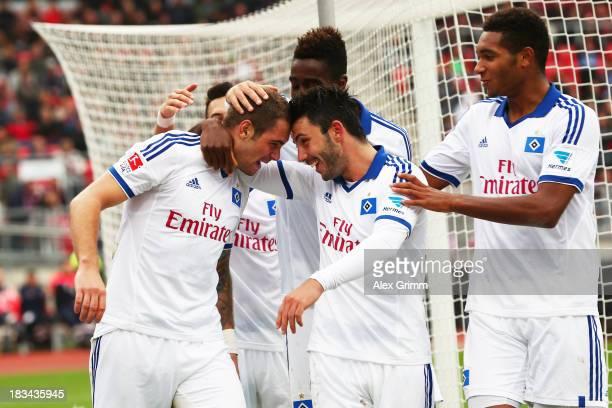 Pierre-Michel Lasogga of Hamburg celebrates his team's fourth goal with team mates Tolgay Arslan and Jonathan Tah during the Bundesliga match between...