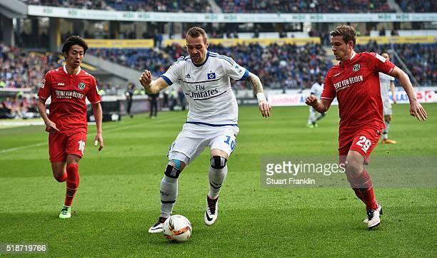 PierreMichel Lasogga of Hamburg is challenged by Ádám Szalai of Hannover during the Bundesliga match between Hannover 96 and Hamburger SV at HDIArena...