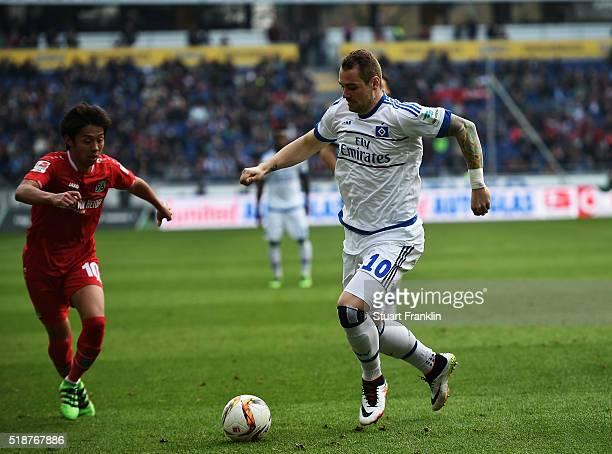 PierreMichel Lasogga of Hamburg is challenged by Hiroshi Kiyotake of Hannover during the Bundesliga match between Hannover 96 and Hamburger SV at...