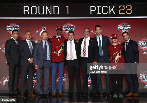 PierreOlivier Joseph poses onstage with team personnel after being selected 23rd overall by the Arizona Coyotes during Round One of the 2017 NHL...